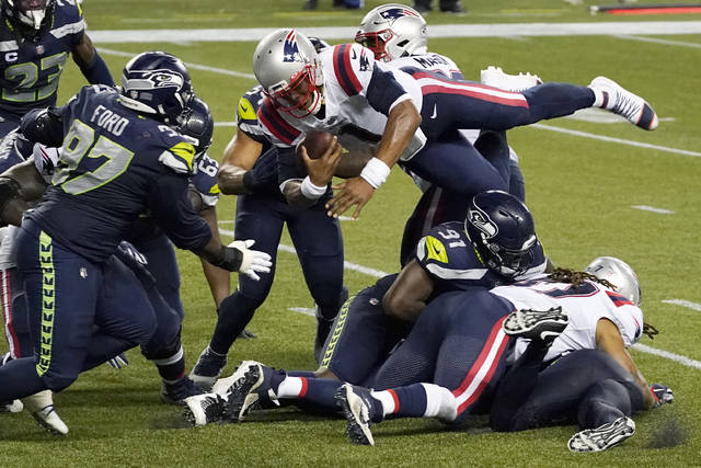 New England Patriots quarterback Cam Newton dives with the ball but is stopped near the goal line as the clock expires in the fourth quarter of an NFL football game against the Seattle Seahawks, Sunday, Sept. 20, 2020, in Seattle. The Seahawks won 35-30. (AP Photo/Elaine Thompson)