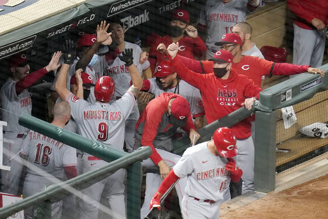 Cincinnati Reds' Mike Moustakas (9) is greeted in the dugout after his solo home run off Minnesota Twins pitcher Edwar Colina during the ninth inning of a baseball game Friday, Sept. 25, 2020, in Minneapolis. (AP Photo/Jim Mone)