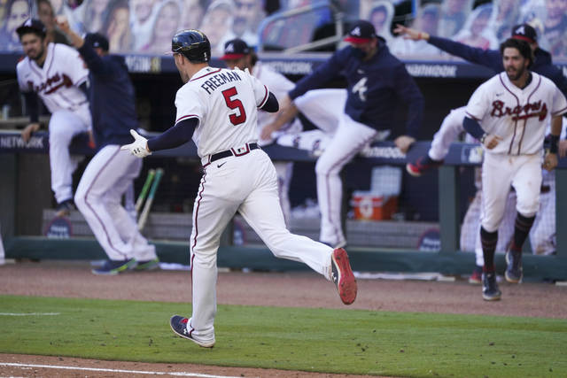 Atlanta Braves Freddie Freeman (5)runs the to first after hiting a game-winning base hit against the Cincinnati Reds in the 13th inning during Game 1 of a National League wild-card baseball series, Wednesday, Sept. 30, 2020, in Atlanta. The Atlanta Braves won 1-0. (AP Photo/John Bazemore)