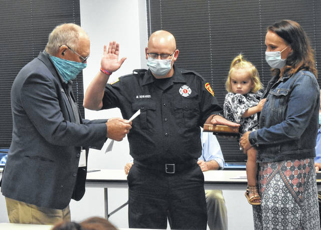 Michael Sowards, center, is sworn-in by Mayor John Stanforth, left, with his hand on a Bible being held by his wife, Kelly, and daughter, Kalhi.