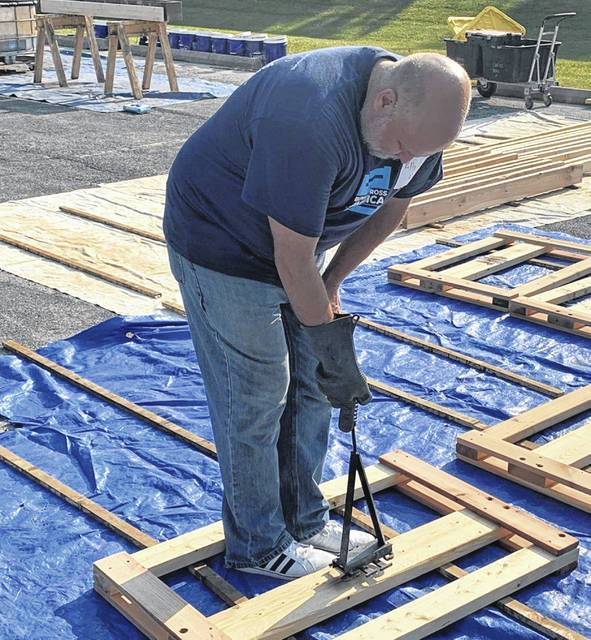 Kelly Kirk brands a bed board during the Sleep in Heavenly Peace bed building on Saturday at Clinton Memorial Hospital.