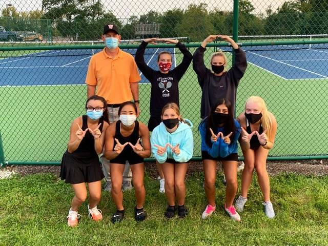 """Wilmington High School tennis players and coach Doug Cooper form a 100 in the back row and """"W"""" signs in the front in honor of Cooper winning the 100th match of his WHS girls tennis coaching career Thursday against New Richmond."""