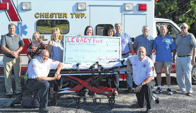Legacy Fund Committee members join representatives of Chester Township Fire & EMS plus the Board of Chester Township Trustees to celebrate the purchase of a cot for the Chester Township life squad service. From left in the front kneeling next to a cot are Scott Flynn and Chief Chuck Whipple; and from left in the back are Mike McCarty, Michelle Morrison, Janet Dixon, Michele Whipple, Chester Township Fiscal Officer Karla Collett, Township Trustees Steve Collett and Rusty Rich, along with Joe Hete, and Tony Long.