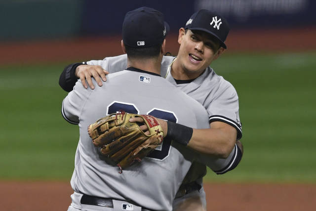 New York Yankees' Gio Urshela (29) and Mike Ford celebrate after the Yankees defeated the Cleveland Indians 10-9 in Game 2 of an American League wild-card baseball series, early Thursday, Oct. 1, 2020, in Cleveland. (AP Photo/David Dermer)