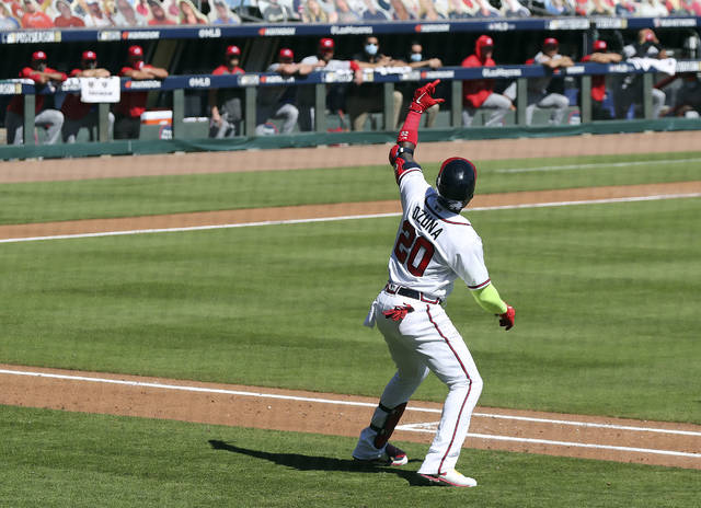 Atlanta Braves' Marcell Ozuna pretends to take a selfie as he heads down the first baseline after hitting a two-run home run in the eighth inning against the Cincinnati Reds in Game 2 of a National League wild-card baseball series, Thursday, Oct. 1, 2020, in Atlanta. (Curtis Compton/Atlanta Journal-Constitution via AP)