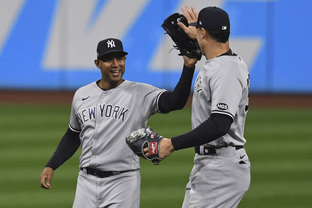 New York Yankees' Aaron Hicks, left, and Aaron Judge celebrate after the Yankees defeated the Cleveland Indians 10-9 in Game 2 of an American League wild-card baseball series, early Thursday, Oct. 1, 2020, in Cleveland. (AP Photo/David Dermer)