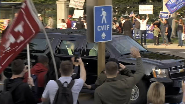 In this image from video, President Donald Trump waves as he drives past supporters gathered outside Walter Reed National Military Medical Center in Bethesda, Md., Sunday, Oct. 4, 2020. Trump was admitted to the hospital after contracting COVID-19. (AP Photo/Carlos Vargas)