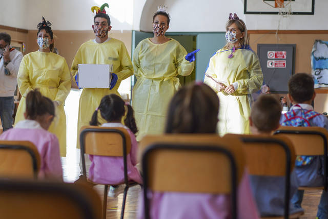 Medical personnel talk to children as they prepare them to receive non-invasive Covid 19 tests with chewing gum at the G.B. Grassi school, in Fiumicino, near Rome, Tuesday, Oct. 6, 2020. (AP Photo/Andrew Medichini)