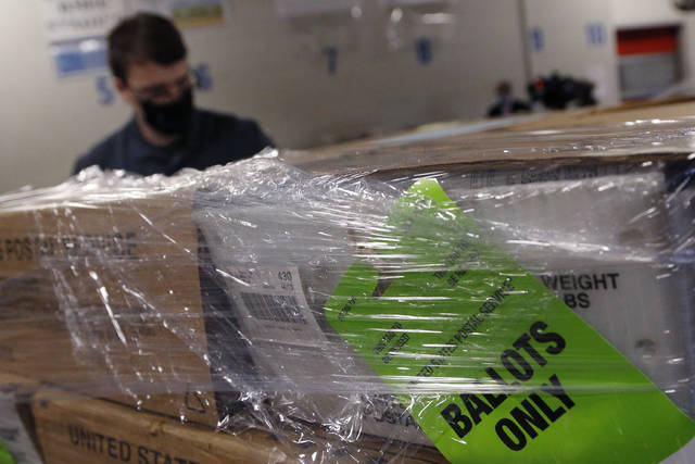 Franklin County Board of Elections employee Braydon Galliers delivers blank absentee ballots to the U.S. Postal Service Monday, Oct. 5, 2020, in Columbus, Ohio. The ballots are being mailed on Tuesday, the first day of early voting for Ohio in the Nov. 3 election. (AP Photo/Jay LaPrete)