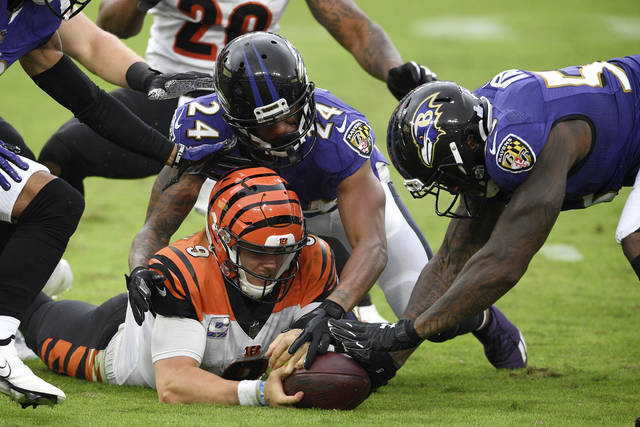 Cincinnati Bengals quarterback Joe Burrow, bottom left, tries to retrieve his fumble as Baltimore Ravens cornerback Marcus Peters (24) and defensive end Jihad Ward (53) challenge him for the recovery during the second half of an NFL football game, Sunday, Oct. 11, 2020, in Baltimore. The ball bounced out of bounds and the Bengals retained possession. (AP Photo/Nick Wass)