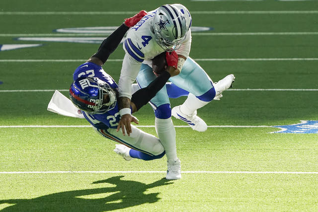 Dallas Cowboys quarterback Dak Prescott (4) is brought down by New York Giants cornerback Logan Ryan (23) during the third quarter of an NFL football game on Sunday, Oct. 11, 2020, in Arlington. Prescott was injured o the play when Ryan came down on his right leg and left the game. (Smiley N. Pool/The Dallas Morning News via AP)