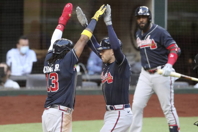 Atlanta Braves first baseman Freddie Freeman, right, celebrates his two-run home run with teammate Ronald Acuna (13) against the Los Angeles Dodgers during the fourth inning in Game 2 Tuesday, Oct. 13, 2020,  in the best-of-seven National League Championship Series at Globe Life Field in Arlington, Texas. (Curtis Compton/Atlanta Journal-Constitution via AP)