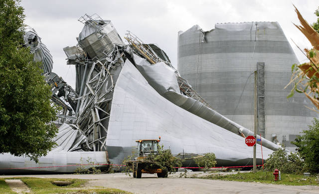 Iowa Department of Transportation workers help with tree debris removal as grain bins from the Archer Daniels Midland facility are seen severely damaged in Keystone, Iowa, on Wednesday, Aug. 12, 2020. Damage estimates from a rare wind storm that slammed Iowa and some other parts of the Midwest in August are growing, with the total now at $7.5 billion, according to a new report. (Jim Slosiarek/The Gazette via AP)