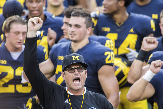 """FILE  - In this Aug. 26, 2018, file photo, Michigan head coach Jim Harbaugh leads his players and fans in singing """"Hail to the Victors"""" after a practice session by the NCAA college football team at Michigan Stadium in Ann Arbor, Mich. Jim Harbaugh enters his sixth season as Michigan's coach with just two years left on his contract, adding another layer of interest in the 18th-ranked Wolverines as they kick off the season this week at No. 21 Minnesota.(AP Photo/Tony Ding, File)"""