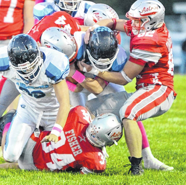 East Clinton's Ethan Kessler (44), Brandon Zimmerman (82) and Brody Fisher (34) bring down a Blanchester ball carrier during last week's game.