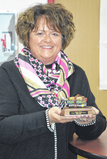 Teresa Butler, who recently retired from teaching at Clinton-Massie, holds a memento from the district.