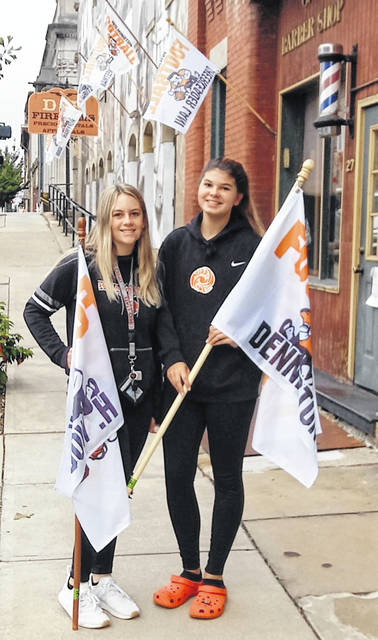 Wilmington High School cheerleaders Elizabeth Custis and Breanna Barnett place spirit flags downtown Friday morning as the 'Cane were set to take on county rival Clinton-Massie.