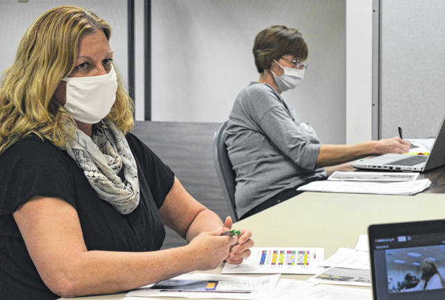 Clinton County Health Commissioner Pam Bauer, left foreground, reports to the Clinton County Board of Health. Tansy Bernard with the Clinton County Health Department is pictured in the background.