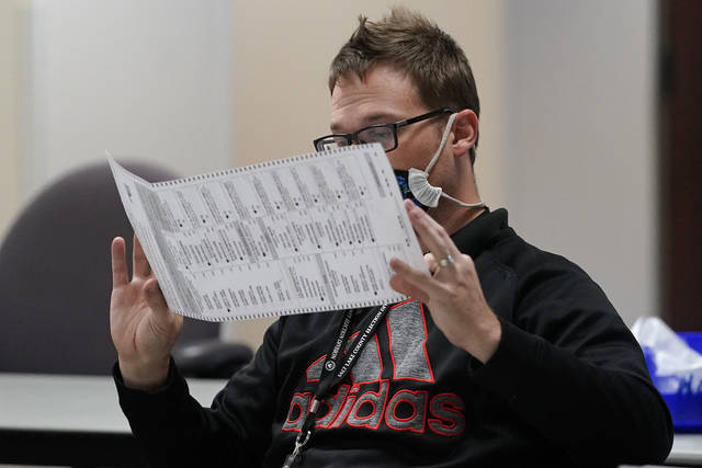 An election worker checks ballots in the elections management center at Salt Lake County Government Center Tuesday, Nov. 3, 2020, in Salt Lake City. . (AP Photo/Rick Bowmer)