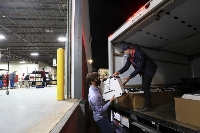 Hamilton County election department employees unload ballot boxes from delivery trucks at the Hamilton County Board of Elections, Tuesday, Nov. 3, 2020, in Norwood, Ohio. (AP Photo/Aaron Doster)