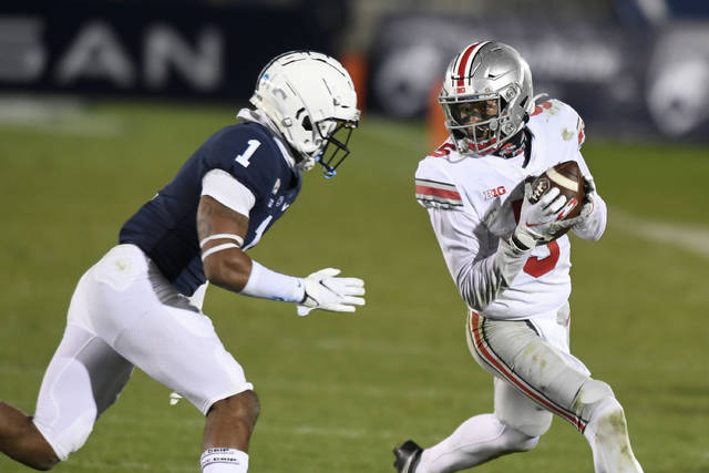Ohio State wide receiver Garrett Wilson (5) catches a pass in front of Penn State safety Jaquan Brisker (1) during the fourth quarter of an NCAA college football game in State College, Pa., Saturday, Oct. 31, 2020. Ohio State won 38-25. (AP Photo/Barry Reeger)