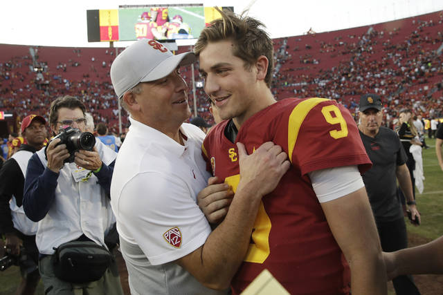 FILE - In this Nov. 23, 2019 file photo, Southern California head coach Clay Helton, left, smiles at quarterback Kedon Slovis (9) after a 52-35 win over UCLA in an NCAA college football game in Los Angeles. BOth Helton and now-sophomore Slovis will return in November. (AP Photo/Marcio Jose Sanchez, File)