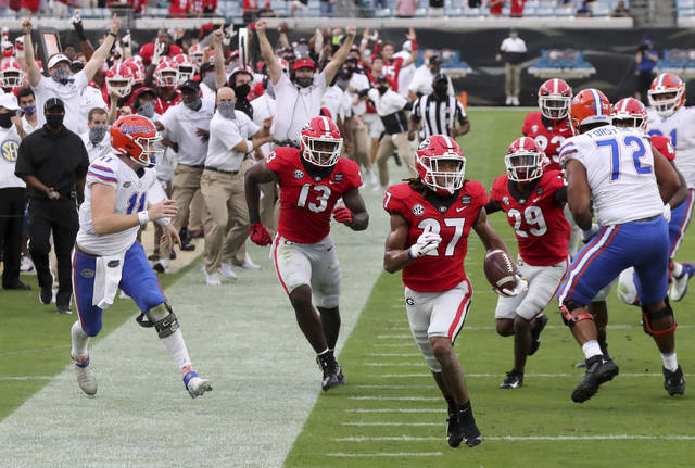 Georgia defensive back Eric Stokes (27) returns an interception for a touchdown during the second quarter of a NCAA college football, Saturday, Nov. 7, 2020, in Jacksonville, Fla. (Curtis Compton/Atlanta Journal-Constitution via AP)