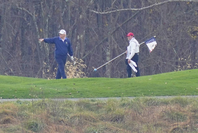 President Donald Trump, left, gesturing while playing golf at Trump National Golf Club in Sterling, Va., as seen from the other side of the Potomac River in Darnestown, Md., Sunday, Nov. 15, 2020. (AP Photo/Manuel Balce Ceneta)