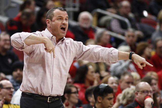 FILE - In this Feb. 27, 2020, file photo, Louisville coach Jeff Walz yells to players during the first half of the team's NCAA college basketball game against Boston College in Louisville, Ky. Walz knows that games will be lost at the last minute this season because of the coronavirus. So he set up a group text with fellow coaches at about a dozen schools that are within driving distance. The premise is that if a team loses a game late, they have a quick way to see if someone else needed a game. (AP Photo/Wade Payne, File)