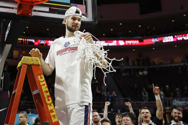 FILE - In this March 10, 2020, file photo, Gonzaga's Killian Tillie (33) cuts down the net after defeating Saint Mary's in an NCAA college basketball game in the final of the West Coast Conference men's tournament in Las Vegas. As more than 300 teams prepare to start a season that will look nothing like any before it, the conversation is not so much about who will be cutting nets at the end of March Madness, as whether anyone will cut nets at all. (AP Photo/John Locher, File)