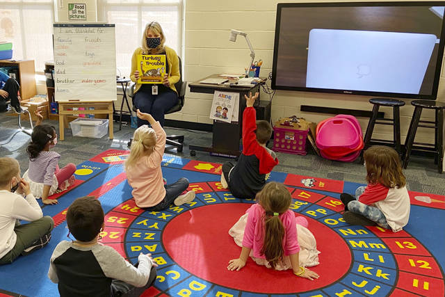 "In this photo provided by Julie Mackett, the kindergarten teacher conducts her class at Ft. Meigs Elementary School, in Perrysburg, Ohio. Contact tracing and isolation protocols meant to contain the spread of the coronavirus are sidelining school employees and frustrating efforts to continue in-person learning. ""I think everybody understands when you can't have enough subs to fill the roles, it's also a safety issue: You can't have that many children without support from adults,"" said Mackett, who went through her own two-week quarantine early in the school year after a student tested positive. (Courtesy of Julie Mackett via AP)"