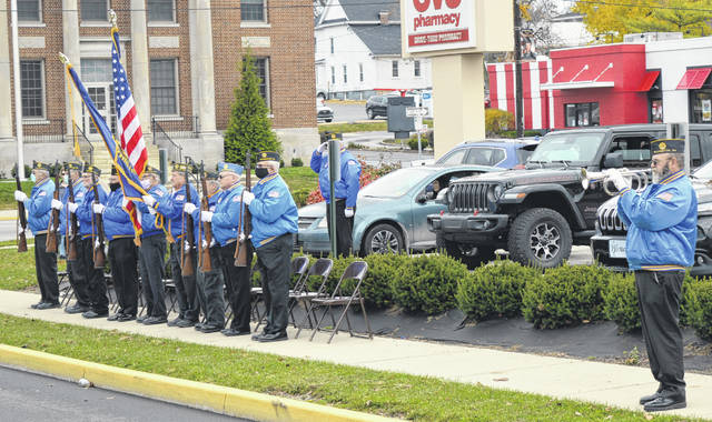 "Local veterans and other residents attend the ceremony. The Veterans Post 49 Honor Guard during the playing of ""Taps."""