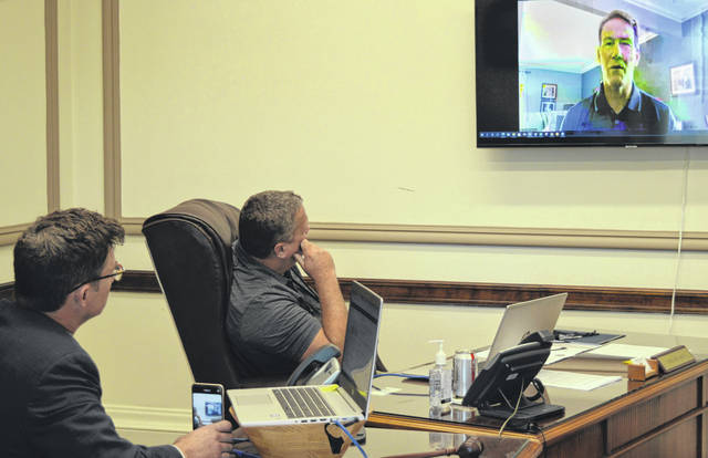 From left, Clinton County Commissioners President Kerry Steed and Clinton County Commissioner Mike McCarty listen and watch as Ohio Lt. Gov. Jon Husted speaks to them and other county leaders this week via Zoom.