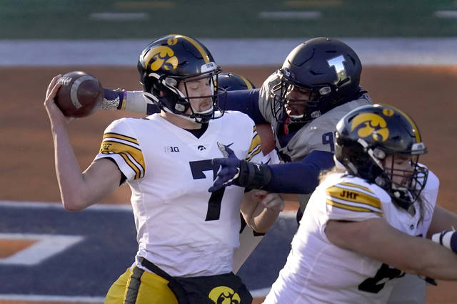 Iowa quarterback Spencer Petras is pressured by Illinois defensive lineman Roderick Perry II during the first half of an NCAA college football game against Illinois Saturday, Dec. 5, 2020, in Champaign, Ill. (AP Photo/Charles Rex Arbogast)