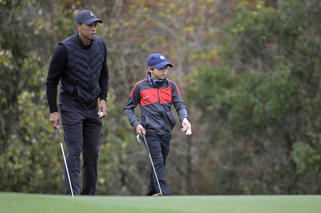 Tiger Woods, left, lines up a putt with his son Charlie on the 11th green during a practice round of the Father Son Challenge golf tournament, Thursday, Dec. 17, 2020, in Orlando, Fla. (AP Photo/Phelan M. Ebenhack)