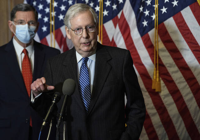 """FILE - In this Tuesday, Dec. 15, 2020, file photo, Senate Majority Leader Mitch McConnell, of Kentucky, speaks during a news conference with other Senate Republicans on Capitol Hill in Washington, while Sen. John Barrasso, R-Wyoming, listens at left. """"There will be another major rescue package for the American people,"""" McConnell said in announcing an agreement for a relief bill, Sunday, Dec. 20, 2020, that would total almost $900 billion. """"It is packed with targeted policies to help struggling Americans who have already waited too long."""" (Nicholas Kamm/Pool Photo via AP, File)"""