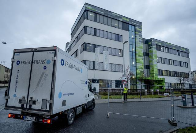 A small truck drives into the German headquarters of the biotechnology company BioNTech is reflected in a mirror in Mainz, Germany, Monday, Dec. 21, 2020. It is expected that the European Medical Agency EMA will allow BioNTechs's vaccin for the European Union on Monday. (AP Photo/Michael Probst)