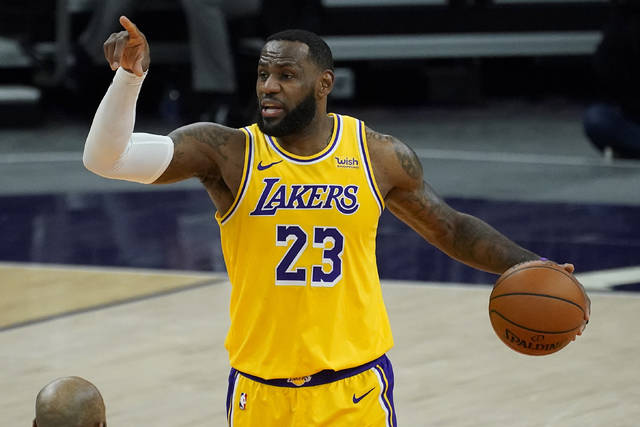 Los Angeles Lakers forward LeBron James (23) calls a play against the Phoenix Suns during the first half of a preseason NBA basketball game, Friday, Dec. 18, 2020, in Phoenix, Ariz. (AP Photo/Matt York)