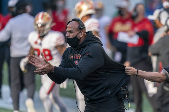 FILE - In this Nov. 1, 2020, file photo, San Francisco 49ers defensive coordinator Robert Saleh cheers on his team from the sideline during the first half of an NFL football game against the Seattle Seahawks in Seattle. One year ago, Saleh and Kansas City Chiefs offensive coordinator Eric Bieniemy missed out on the coaching carousel despite being coordinators of the two Super Bowl teams. The two figure to be near the top of many of the lists of possible head coaching candidates again this offseason when the NFL is hoping some new rules lead to more opportunities for minority coaches.(AP Photo/Stephen Brashear, File)