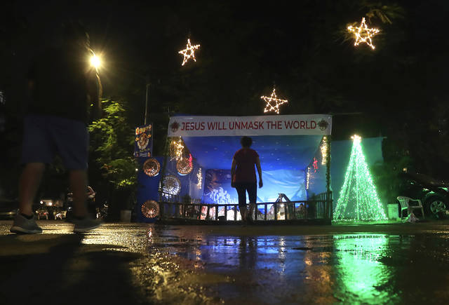 A message that reads 'Jesus will unmask the world' is displayed on a Christmas crib lit up with lights on the eve of Christmas in Mumbai, India, Thursday, Dec. 24, 2020. Though Hindus and Muslims comprise the majority of the population in India, Christmas is a national holiday celebrated with much fanfare. (AP Photo/Rafiq Maqbool)
