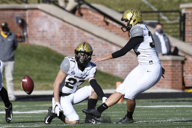 FILE - In this Nov. 28, 2020, file photo, Vanderbilt's Sarah Fuller, right, kicks off as Ryan McCord (27) holds to start the second half of an NCAA college football game against Missouri in Columbia, Mo. With the kick, Fuller became the first female to play in a Southeastern Conference football game. (AP Photo/L.G. Patterson, File)