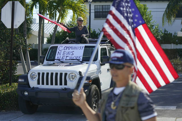 Supporters of President Donald Trump watch his motorcade drive by in West Palm Beach, Fla., Sunday, Dec. 27, 2020. Trump is en route to his Mar-a-Lago resort in Palm Beach, Fla., after visiting Trump International Golf Club. (AP Photo/Patrick Semansky)