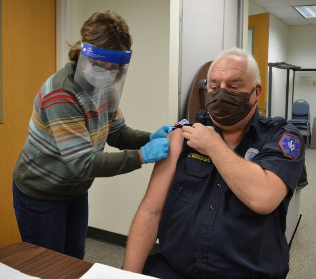 A medical first-responder, Blanchester EMS Chief Jim Burroughs, right, gets a COVID-19 vaccine shot Monday morning at the Clinton County Health Department. Clinton County Health District Director of Nursing Monica Wood, left, administers the shot.