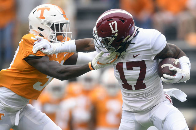 Alabama wide receiver Jaylen Waddle (17) pushes away Tennessee defensive back Kenney Solomon (31) during an NCAA college football game in Knoxville, Tenn., Saturday, Oct. 24, 2020. (Caitie McMekin/Knoxville News Sentinel via AP)