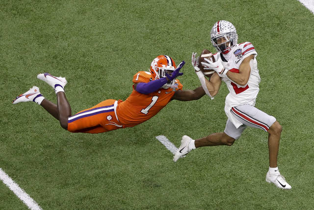 Ohio State wide receiver Chris Olave catches a touchdown pass in front of Clemson cornerback Derion Kendrick during the second half of the Sugar Bowl NCAA college football game Friday, Jan. 1, 2021, in New Orleans. (AP Photo/Butch Dill)