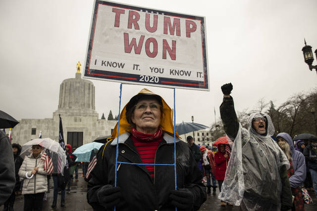 FILE - In this Jan. 6, 2021 file photo, a supporter of President Donald Trump gathers to protest in solidarity in Salem, Ore.    Statehouses where Trump loyalists have rallied since the Nov. 3 election are heightening security after the storming of the U.S. Capitol this week. Police agencies in a number of states are monitoring threats of violence as legislatures return to session and as the nation prepares for the inauguration of President-elect Joe Biden. (AP Photo/Paula Bronstein, File)