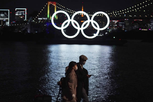 FILE - In this Dec. 1, 2020, file photo, a man and a woman walk past near the Olympic rings floating in the water in the Odaiba section in Tokyo. More than 80% of people in Japan who were surveyed in two polls in the last few days say the Tokyo Olympics should be canceled or postponed, or say they believe the Olympics will not take place. (AP Photo/Eugene Hoshiko, File)