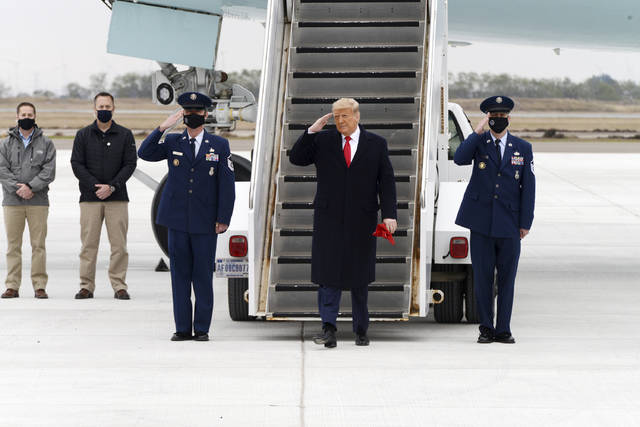 President Donald Trump salutes as he steps off Air Force One upon arrival at Valley International Airport, Tuesday, Jan. 12, 2021, in Harlingen, Texas. (Miguel Roberts/The Brownsville Herald via AP)