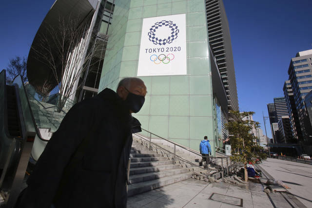 A man walks by the logo of Tokyo Olympic Games planned to start in the summer of 2021, in Tokyo, Tuesday, Jan. 19, 2021. Tokyo organizers have no public program planned to mark the milestone. There is too much uncertainty for that right now. Tokyo and other parts of Japan are under an emergency order because of surging coronavirus cases. (AP Photo/Koji Sasahara)