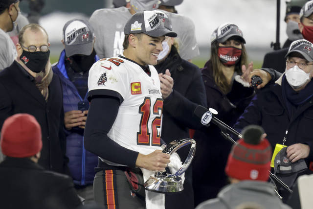 Tampa Bay Buccaneers quarterback Tom Brady (12) holds the championship trophy after winning the NFC championship NFL football game against the Green Bay Packers in Green Bay, Wis., Sunday, Jan. 24, 2021. The Buccaneers defeated the Packers 31-26 to advance to the Super Bowl. (AP Photo/Matt Ludtke)